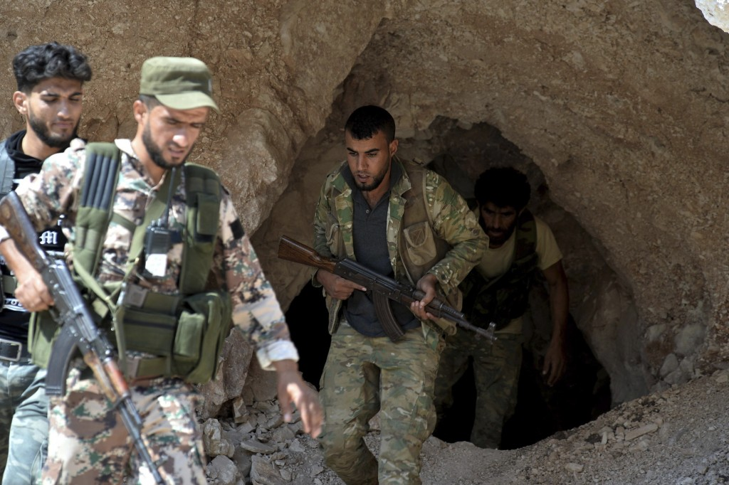 FILE - In this Sept. 9, 2018 file photo, fighters with the Free Syrian army exit a cave where they live, on the outskirts of the northern town of Jisr