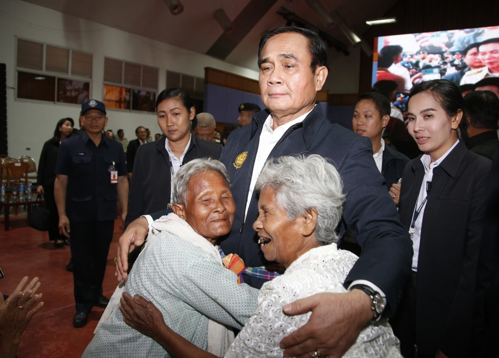 In this March 13, 2019, photo,  elderly locals hug Prime Minister Prayuth Chan-ocha and candidate for the same position, as he attends a government-sp