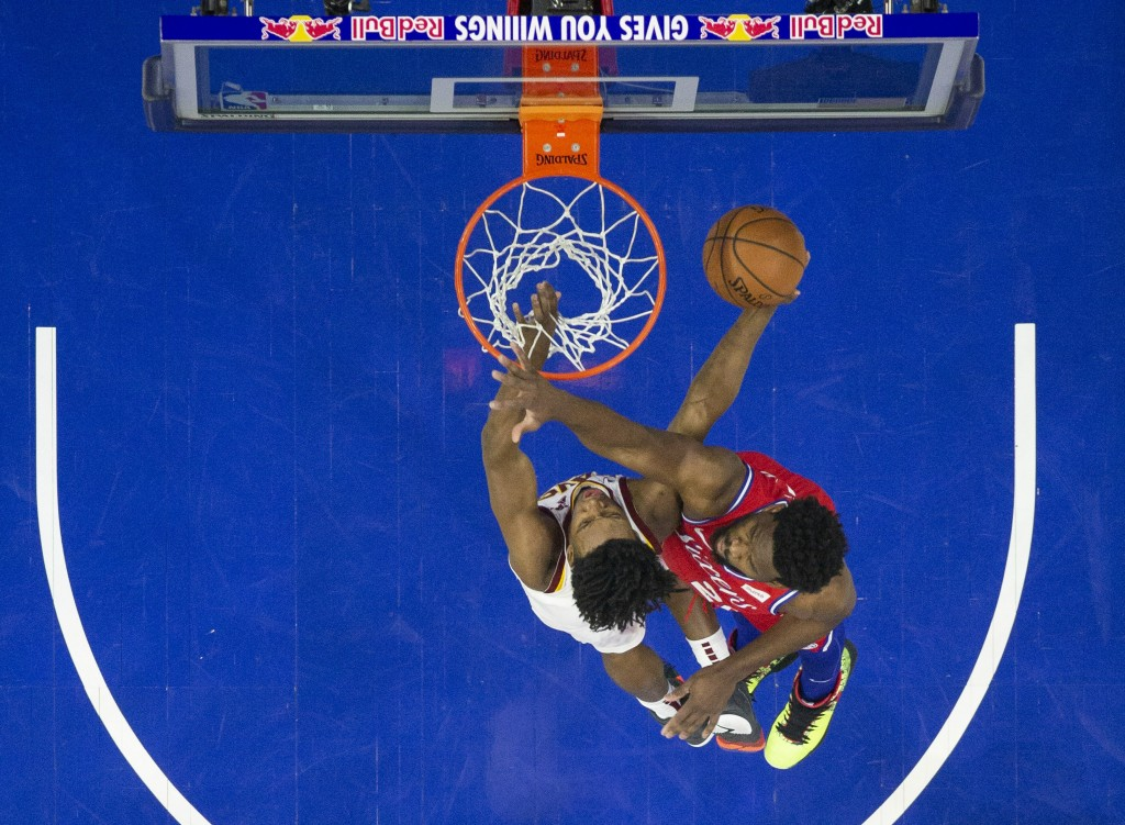 Cleveland Cavaliers&#039 Collin Sexton left shoots against Philadelphia 76ers&#039 Joel Embiid right of Cameroon during the first half of an NBA basketba