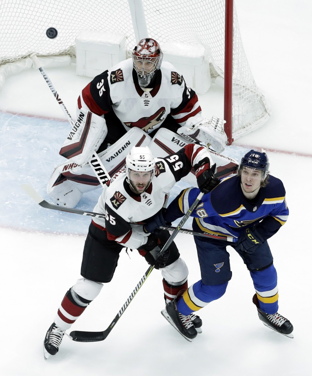 Arizona Coyotes goaltender Darcy Kuemper (35), Jason Demers (55) and St. Louis Blues' Robert Thomas (18) watch as the puck flies in the air during the