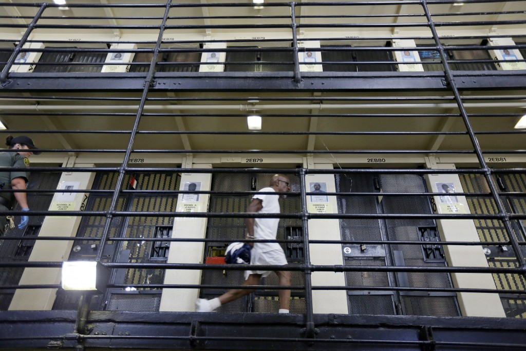 FILE - In this Aug. 16, 2016 file photo, a condemned inmate walks along the east block of death row at San Quentin State Prison in San Quentin, Calif.