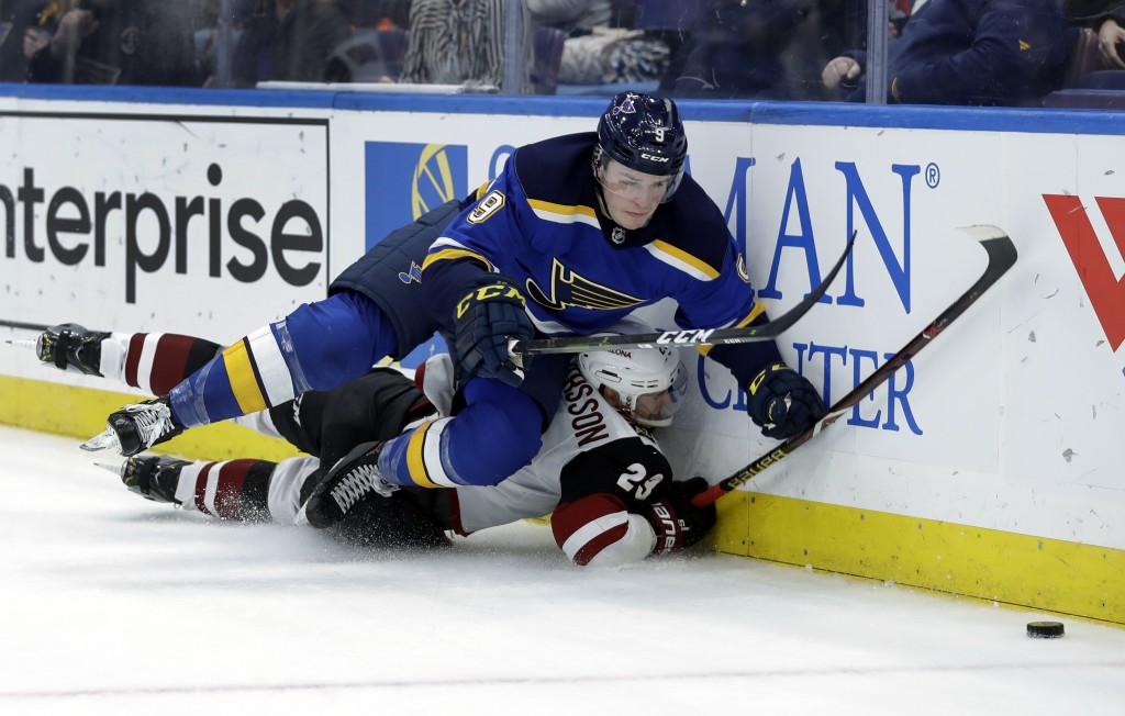 St. Louis Blues' Sammy Blais, top, and Arizona Coyotes' Oliver Ekman-Larsson, of Sweden, slam into the boards as they chase a loose puck during the se