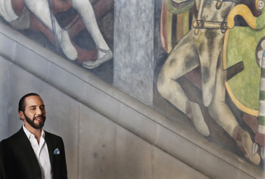 El Salvador's President-elect Nayib Bukele walks past the Diego Rivera murals at Mexico's National Palace after meeting with the President Andres Manu