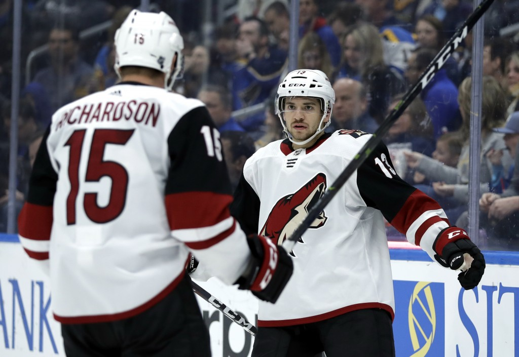 Arizona Coyotes' Vinnie Hinostroza, right, is congratulated by Brad Richardson after scoring during the third period of an NHL hockey game against the