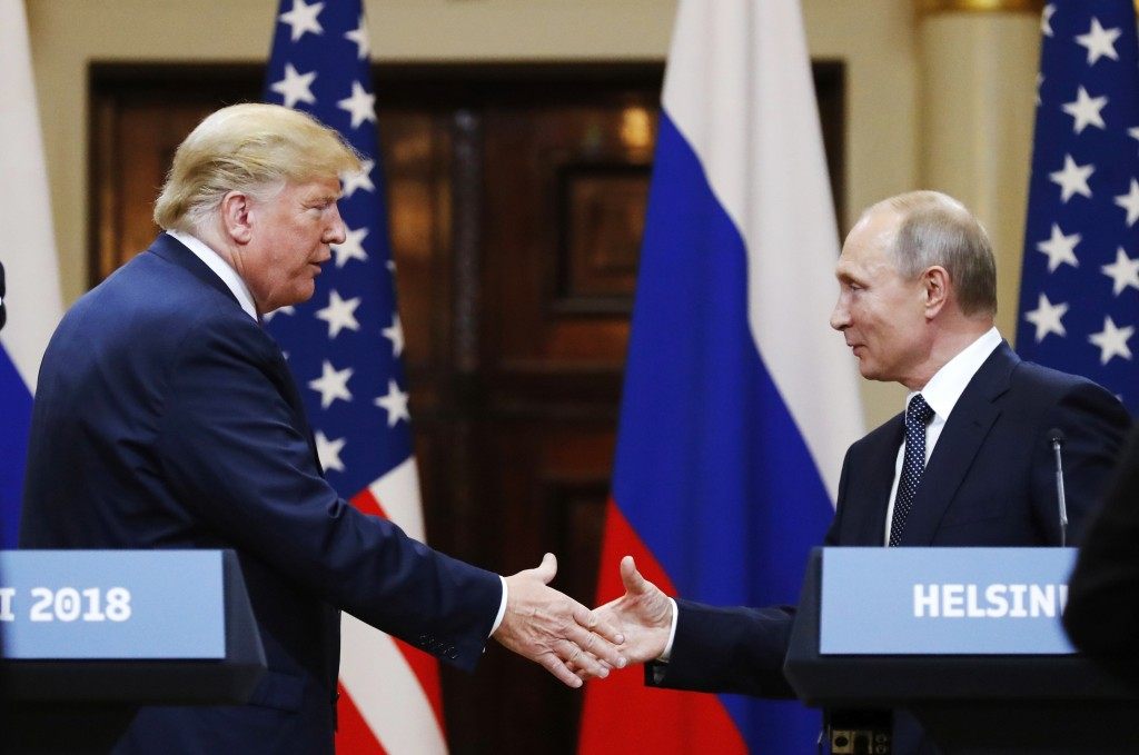 FILE - In this file photo taken on Monday, July 16, 2018, U.S. President Donald Trump, left, shakes hand with Russian President Vladimir Putin at the