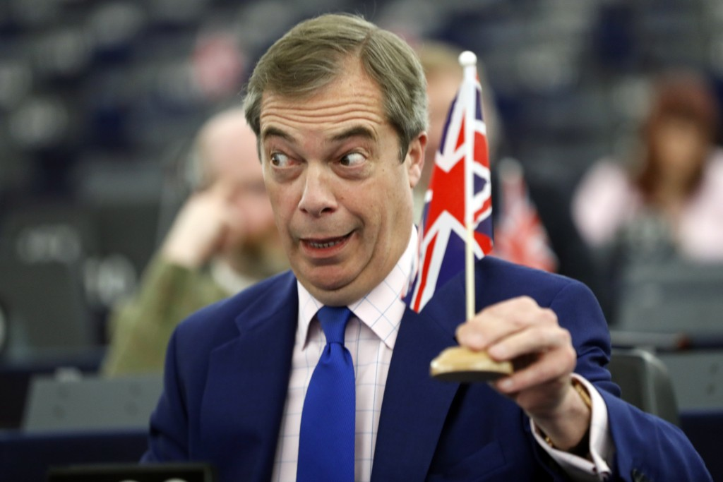 Former U.K. Independence Party (UKIP) leader and member of the European Parliament Nigel Farage holds a U.K. flag during a plenary session at the Euro