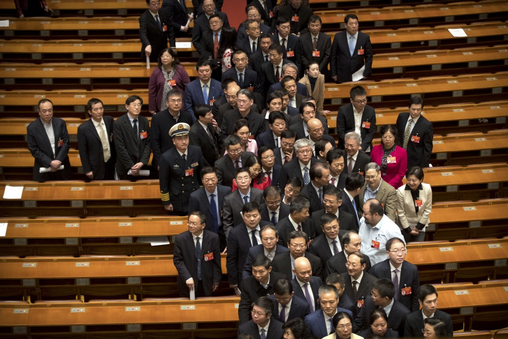 In this March 13, 2019, photo, delegates leave after the closing session of the Chinese People's Political Consultative Conference (CPPCC) at the Grea