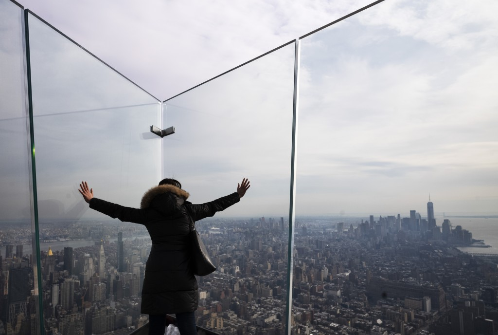 """In this March 8, 2019 photo, a visitor looks through thick glass plates that line a triangular-shaped outdoor observation deck, named """"The Edge"""" at Hu"""