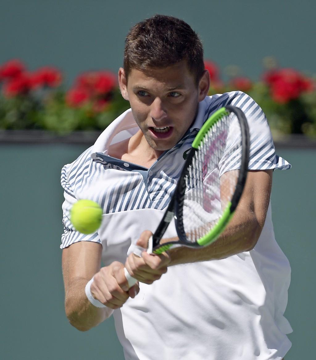 Filip Krajinovic of Serbia returns a shot to Rafael Nadal of Spain at the BNP Paribas Open tennis tournament Wednesday