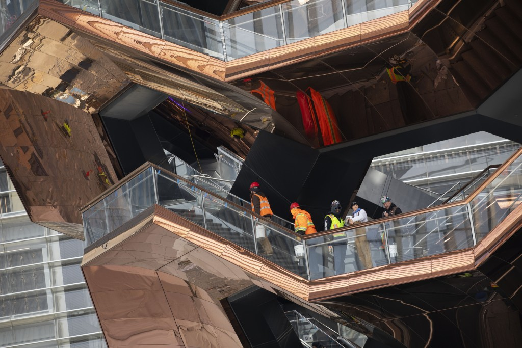 """In this March 8, 2019 photo, workers climb the stairs of the """"Vessel,"""" a 150-foot-tall structure in New York. The Thomas Heatherwick design opens to t"""