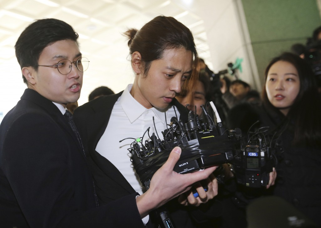 In this March 14, 2019, photo, K-pop singer Jung Joon-young, center, arrives at the Seoul Metropolitan Police Agency in Seoul, South Korea. Police hav