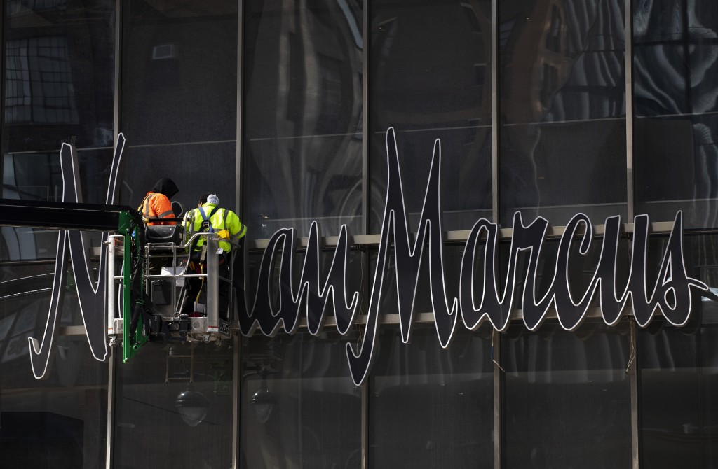 In this March 8, 2019 photo, workers install a sign for the Neiman Marcus department store at the Hudson Yards development in New York. The store and