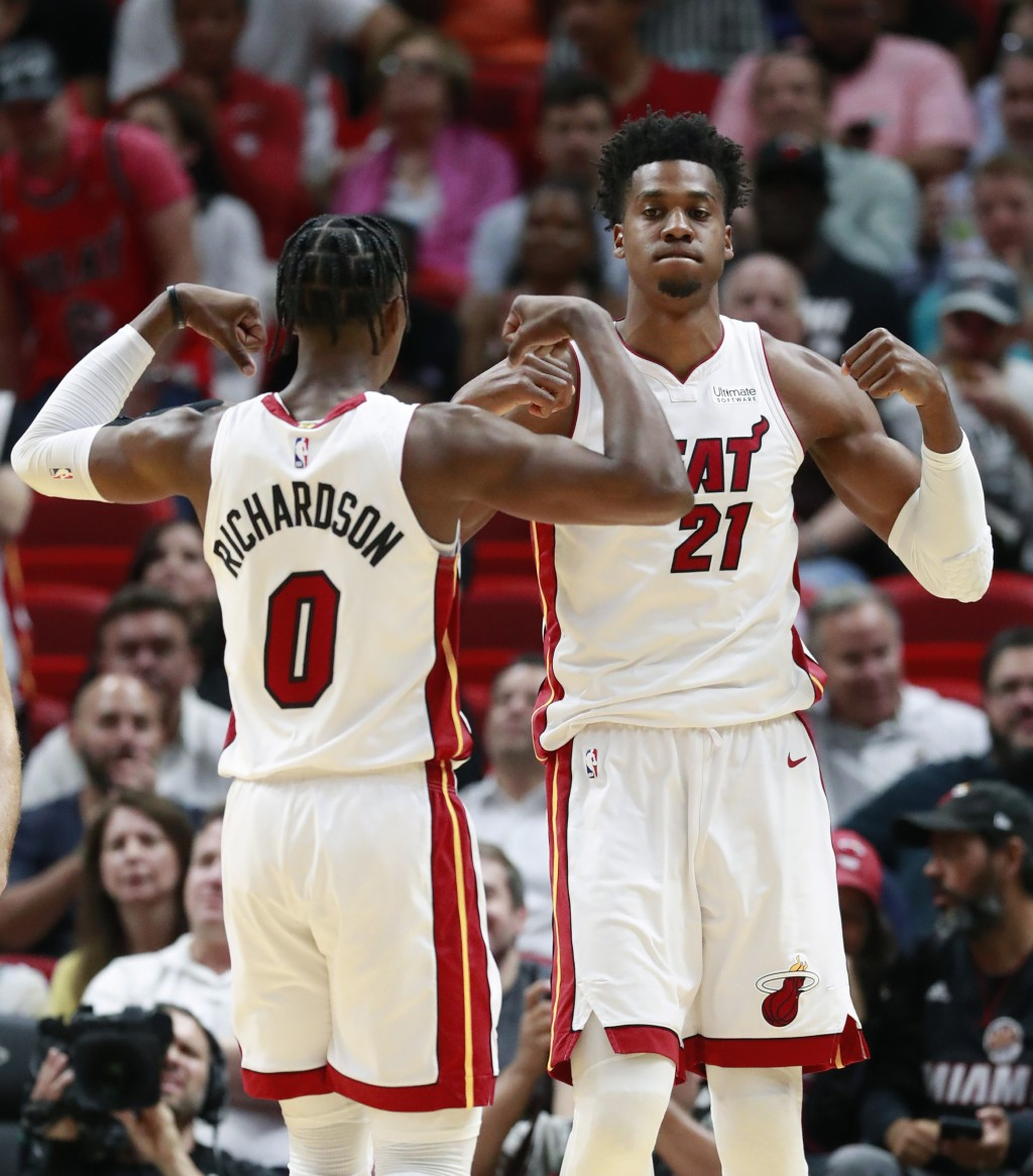 Miami Heat center Hassan Whiteside (21) and guard Josh Richardson (0) celebrate after Whiteside scored during the first half of an NBA basketball game