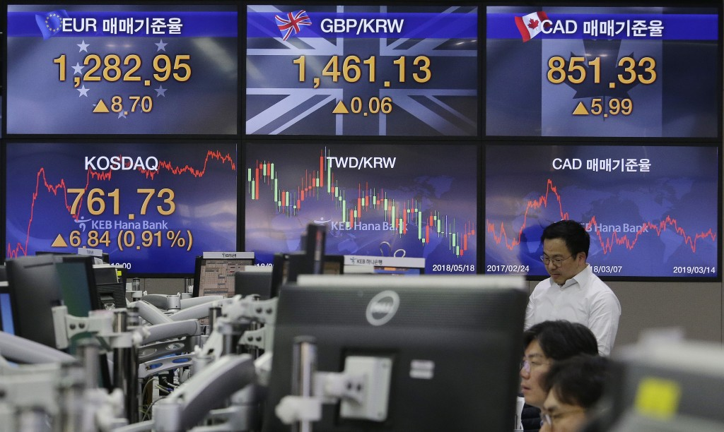 A currency trader watches monitors at the foreign exchange dealing room of the KEB Hana Bank headquarters in Seoul, South Korea, Thursday, March 14, 2...
