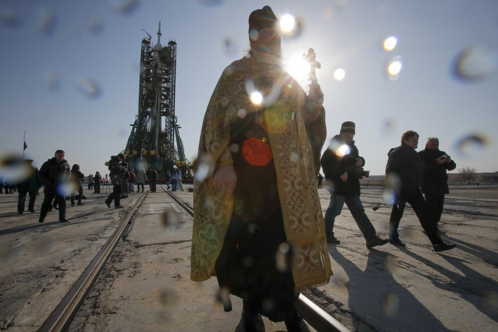 An Orthodox priest walks after a blessing service in front of the Soyuz FG rocket at the Russian leased Baikonur cosmodrome, Kazakhstan, Thursday, Mar