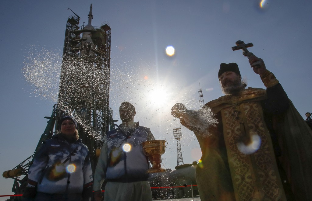 An Orthodox priest conducts a blessing service in front of the Soyuz FG rocket at the Russian leased Baikonur cosmodrome, Kazakhstan, Thursday, March