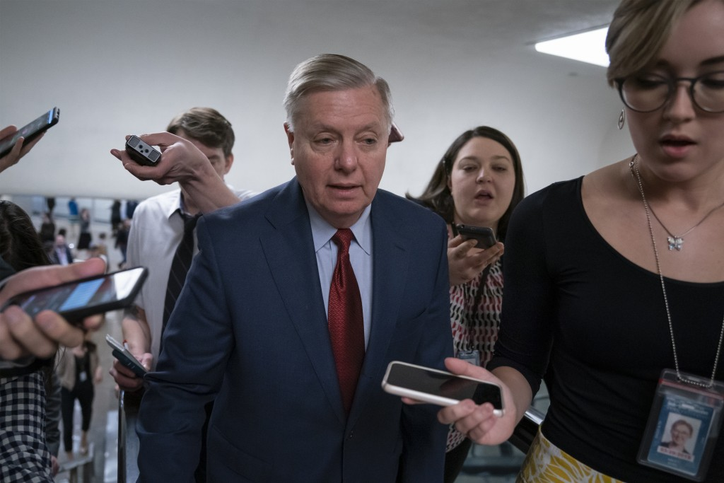 IN this March 13, 2019, photo, reporters pose questions to Sen. Lindsey Graham, R-S.C., at the Capitol in Washington, Wednesday, March 13, 2019. The R