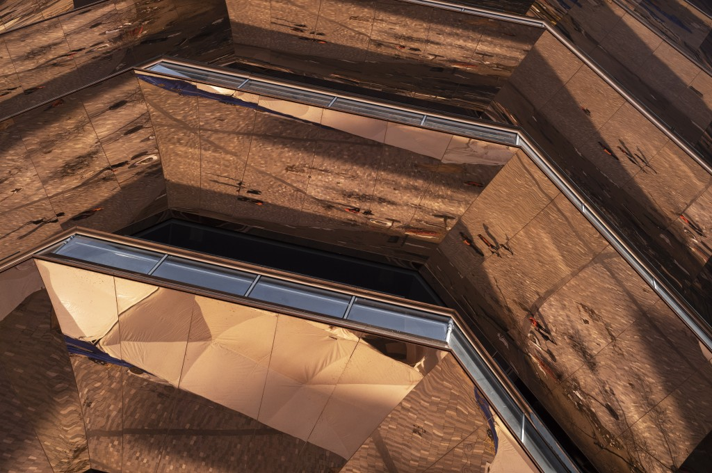 """This March 8, 2019 photo shows the copper-colored skin of the """"Vessel""""  in Hudson Yards in New York. Designed by Thomas Heatherwick, the sculpture has"""