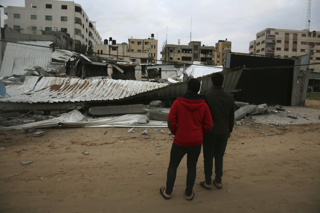 Palestinians check the damage of destroyed building belongs to Hamas ministry of prisoners hit by Israeli airstrikes in Gaza City, early Friday, Frida