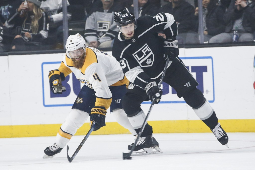 Nashville Predators defenseman Ryan Ellis (4) and Los Angeles Kings forward Dustin Brown (23) vie for the puck during the first period of an NHL hocke