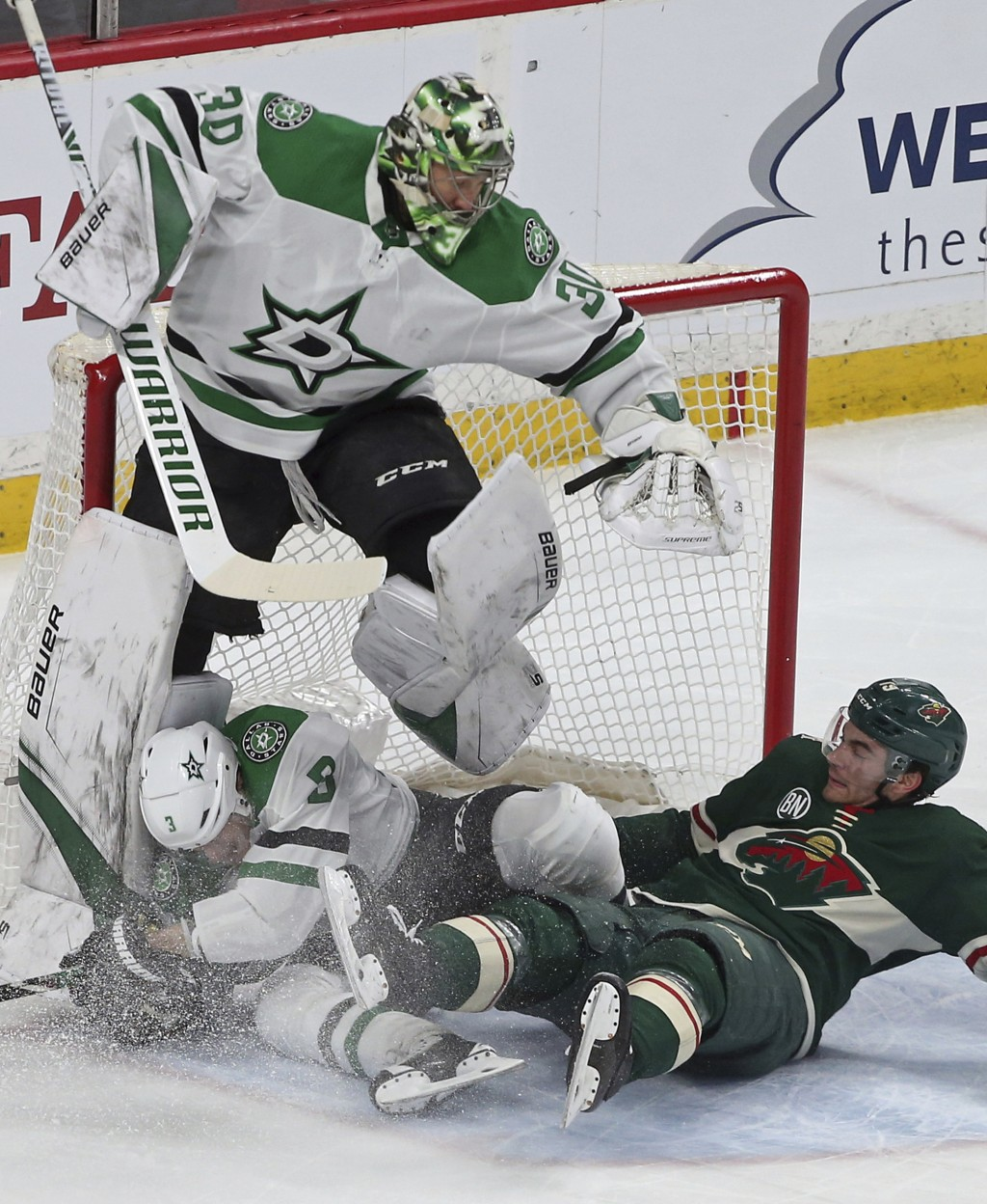 Dallas Stars goalie Ben Bishop, top, jumps to avoid teammate John Klingberg, bottom left, of Sweden, as Minnesota Wild's Luke Kunin, right, crashes in