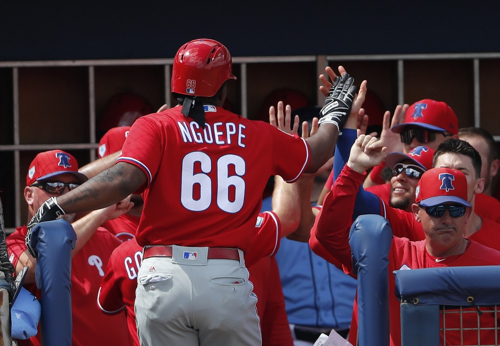 Philadelphia Phillies' Gift Ngoepe (66) celebrates at the dugout entrance after hitting a two-run home run in the seventh inning of a spring training