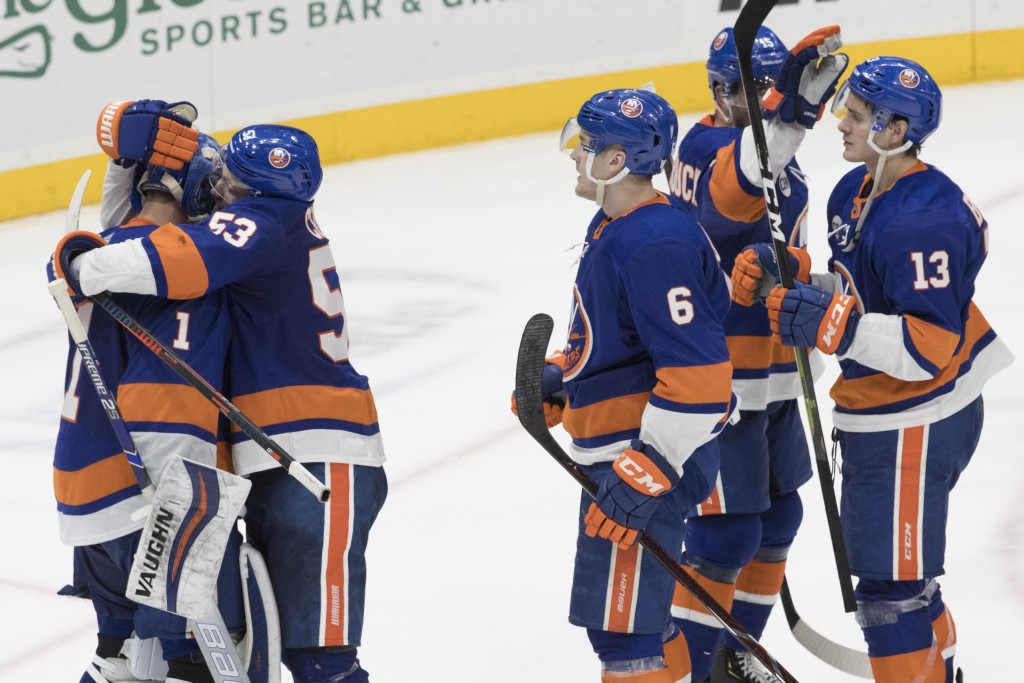 New York Islanders goaltender Thomas Greiss (1) celebrates with his teammates after winning an NHL hockey game against the Montreal Canadiens, Thursda