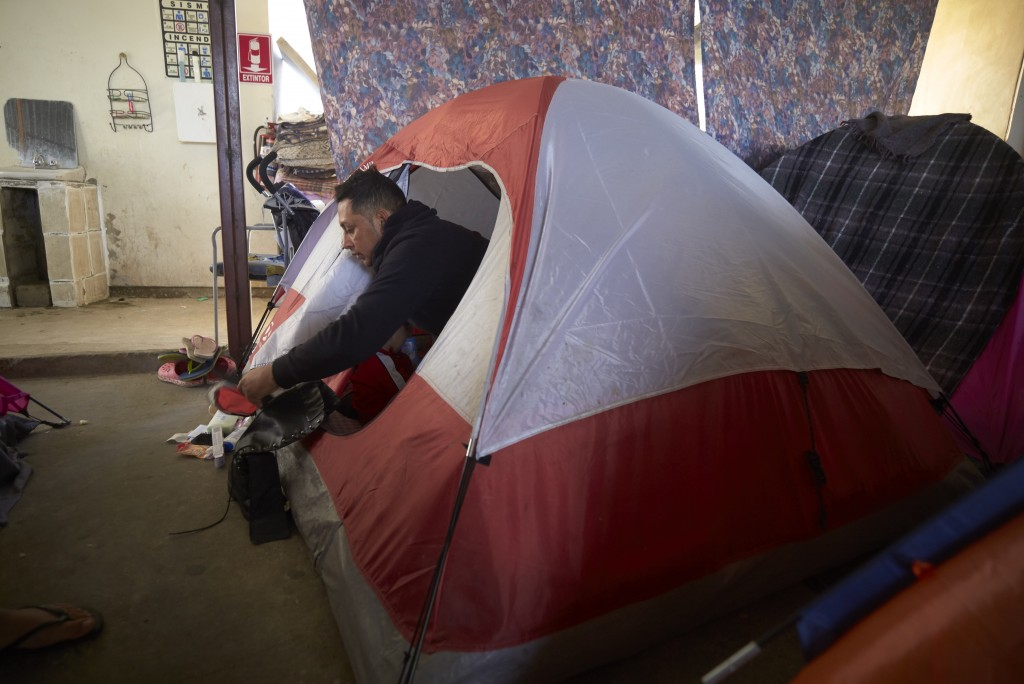 In this March 5, 2019, image, Juan Carlos Perla looks out from the family's tent - a two-person tent where all five members of the family sleep - insi