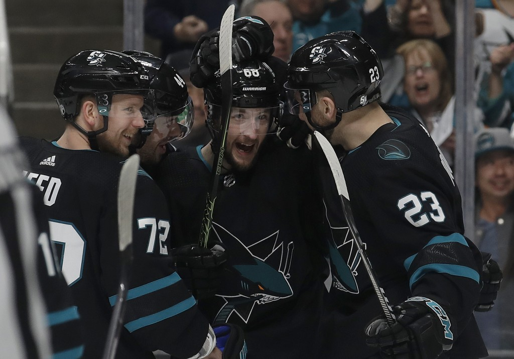 San Jose Sharks center Melker Karlsson, center, is congratulated by teammates after scoring a goal against the Florida Panthers during the first perio
