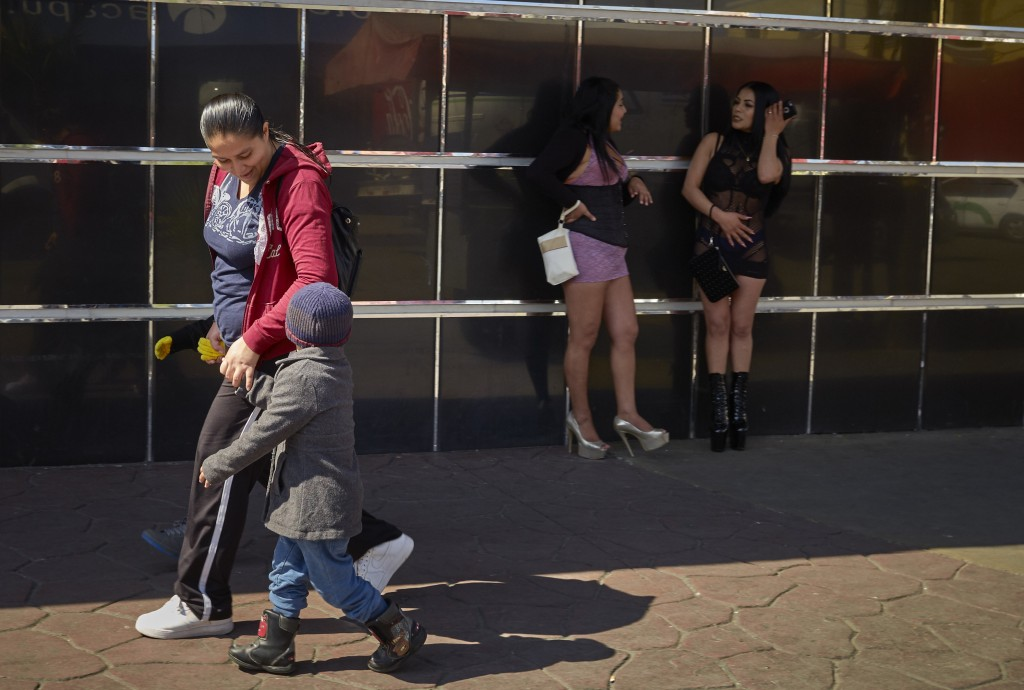 In this March 5, 2019, image, Ruth Aracely Monroy walks with her sons as they pass two women in the red-light district of Tijuana, Mexico. (AP Photo/G