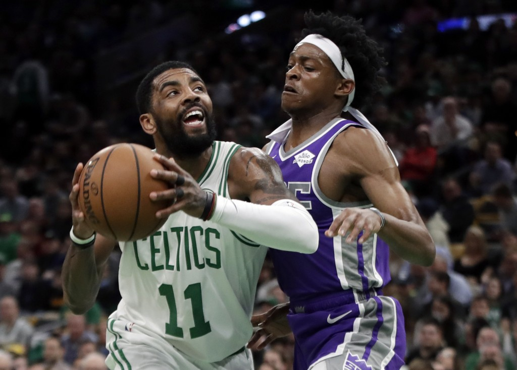Boston Celtics guard Kyrie Irving (11) drives against Sacramento Kings guard De'Aaron Fox in the first half of an NBA basketball game, Thursday, March