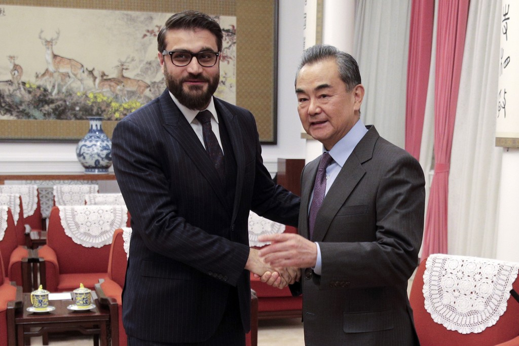 FILE - In this Jan. 10, 2019, file photo, Afghanistan national security adviser Hamdullah Mohib, left, shakes hands with Chinese Foreign Minister Wang