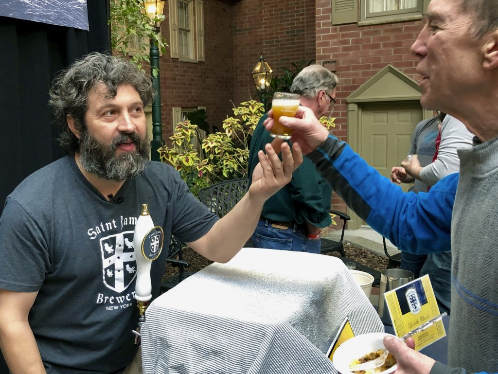 "In this March 9, 2019 photo, Jamie Adams, left, hands out a sample of his new ale called ""Deep Ascent"" at the New York State Craft Brewers Festival in"