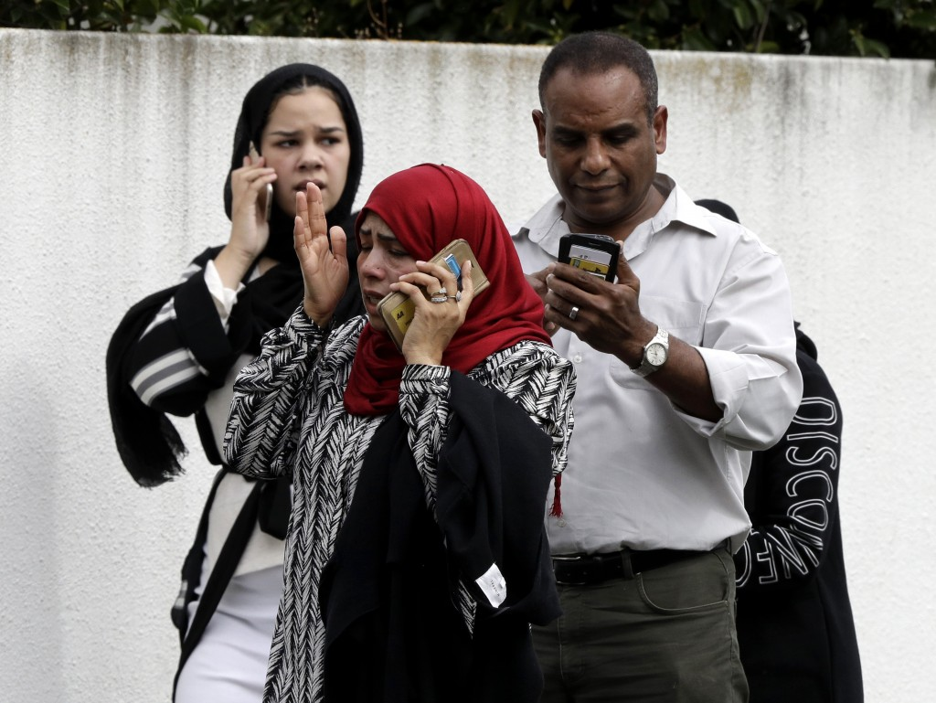 People wait outside a mosque in central Christchurch, New Zealand, Friday, March 15, 2019. Many people were killed in a mass shooting at a mosque, a w