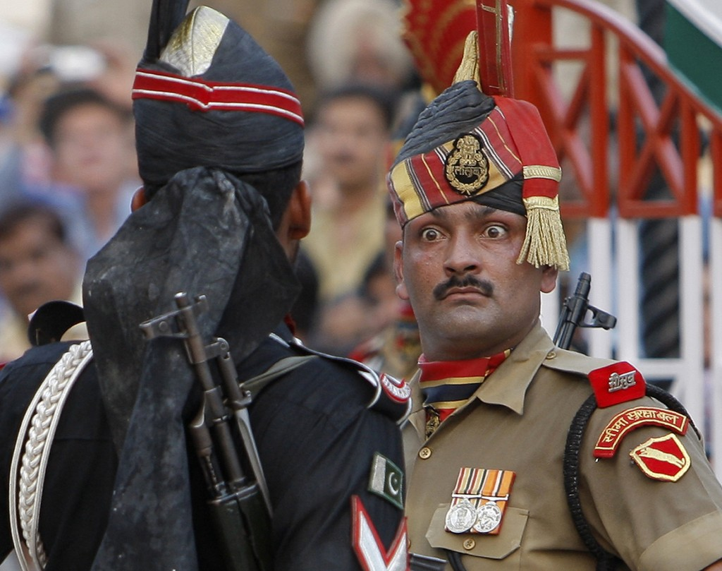 FILE - In this July 19, 2009, file photo, an Indian Border Security Force soldier, right, and a Pakistani Rangers soldier face one another at a daily