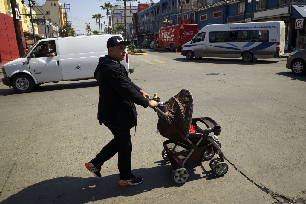 In this March 5, 2019, image, Juan Carlos Perla pushes his youngest son, Joshua, in a stroller along a street in Tijuana, Mexico. Perla's experience s