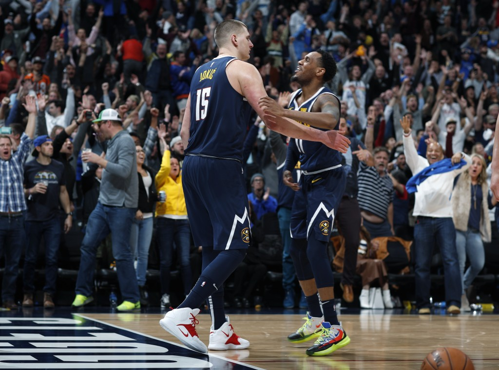Denver Nuggets center Nikola Jokic, left, is congratulated for his game-winning basket by guard Monte Morris during the team's NBA basketball game aga