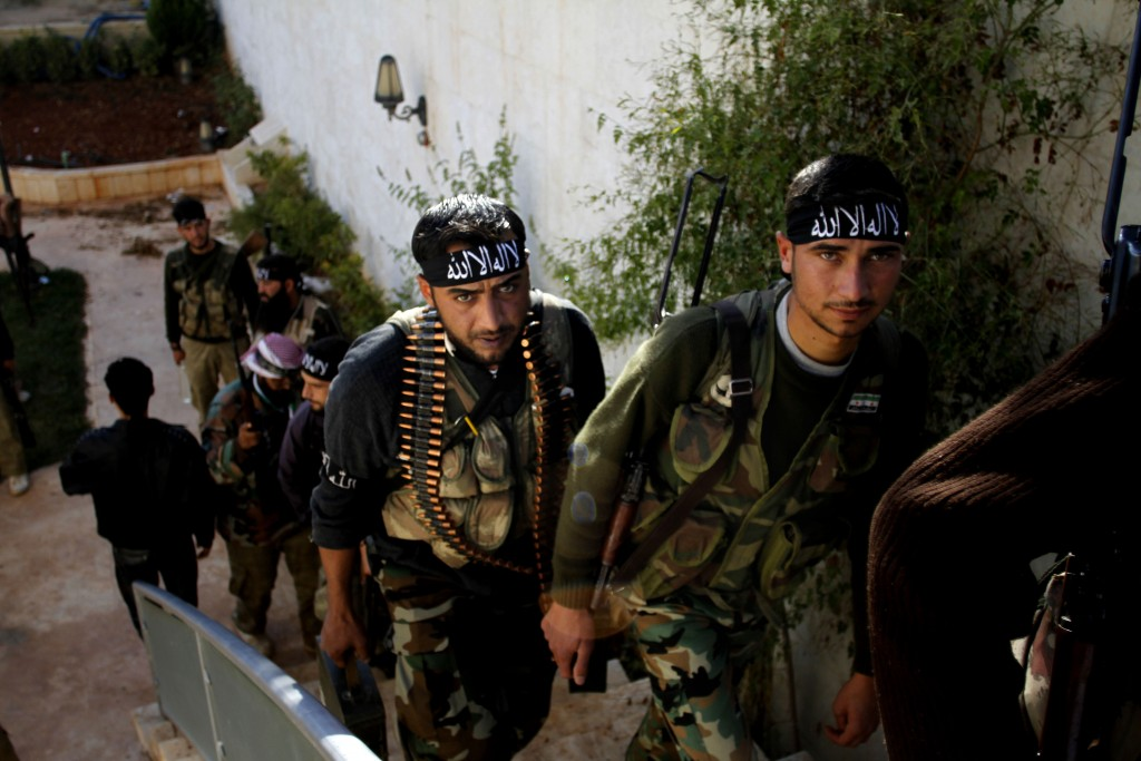 "FILE - In this Nov. 14, 2012 file photo, fighters of ""The Beloved of Allah,"" militia head towards fighting with government forces on the outskirts of"