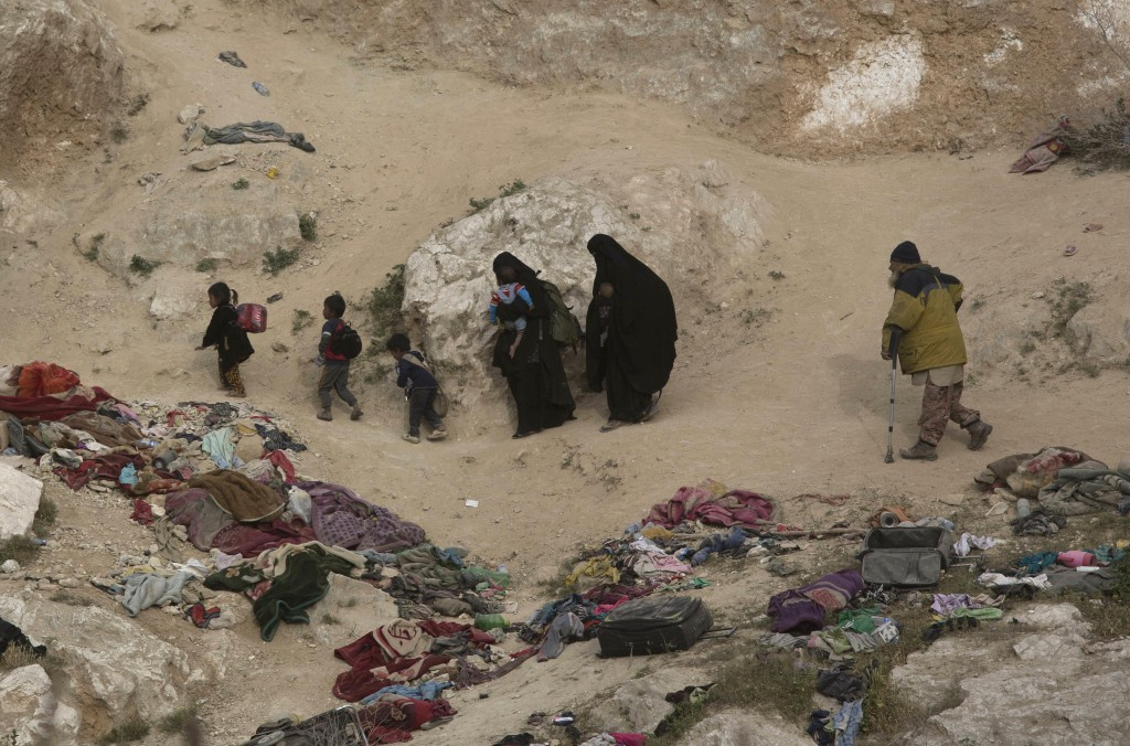 Women, children, and an injured man who left the besieged Islamic State-held village of Baghouz, Syria, scramble over a rocky hillside to be checked b