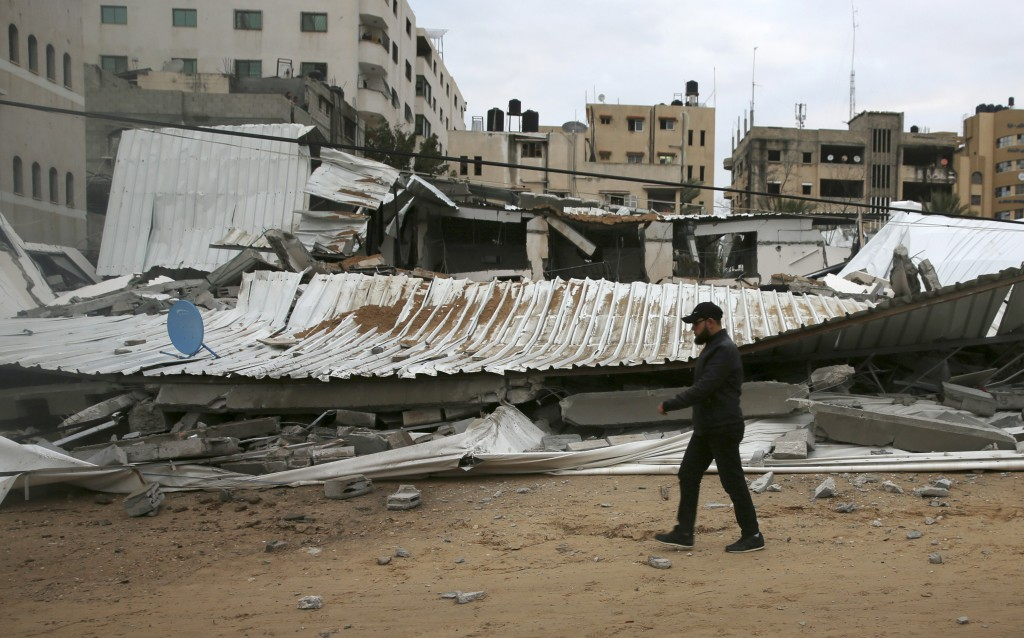 A Palestinian inspects the damage of destroyed building belongs to Hamas ministry of prisoners hit by Israeli airstrikes in Gaza City, early Friday, M