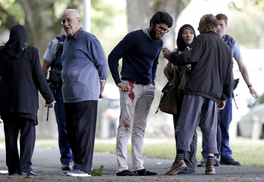 People stand across the road from a mosque in central Christchurch, New Zealand, Friday, March 15, 2019. A witness says a number of people have been k