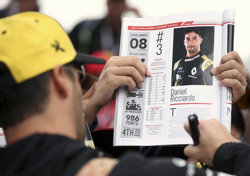 Renault driver Daniel Ricciardo of Australia signs autographs as he arrives at the track of the Australian Grand Prix in Melbourne, Australia, Friday,