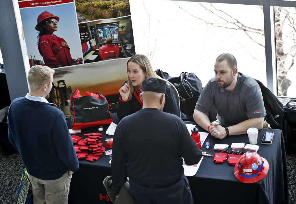 In this March 7, 2019, photo visitors to the Pittsburgh veterans job fair meet with recruiters at Heinz Field in Pittsburgh. On Friday, March 15, the