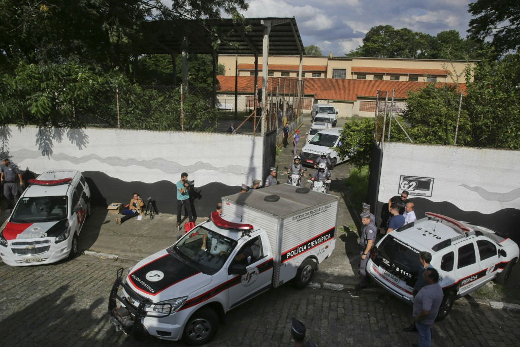 A fleet of funeral vans transport the bodies of the people who were killed in a school shooting at the Raul Brasil State School in Suzano, Brazil, on