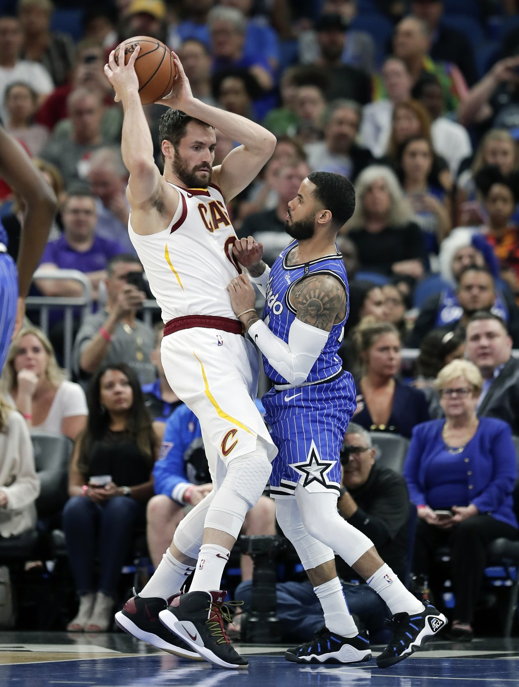 Cleveland Cavaliers' Kevin Love, left, looks to pass the ball as he is guarded by Orlando Magic's D.J. Augustin during the first half of an NBA basket