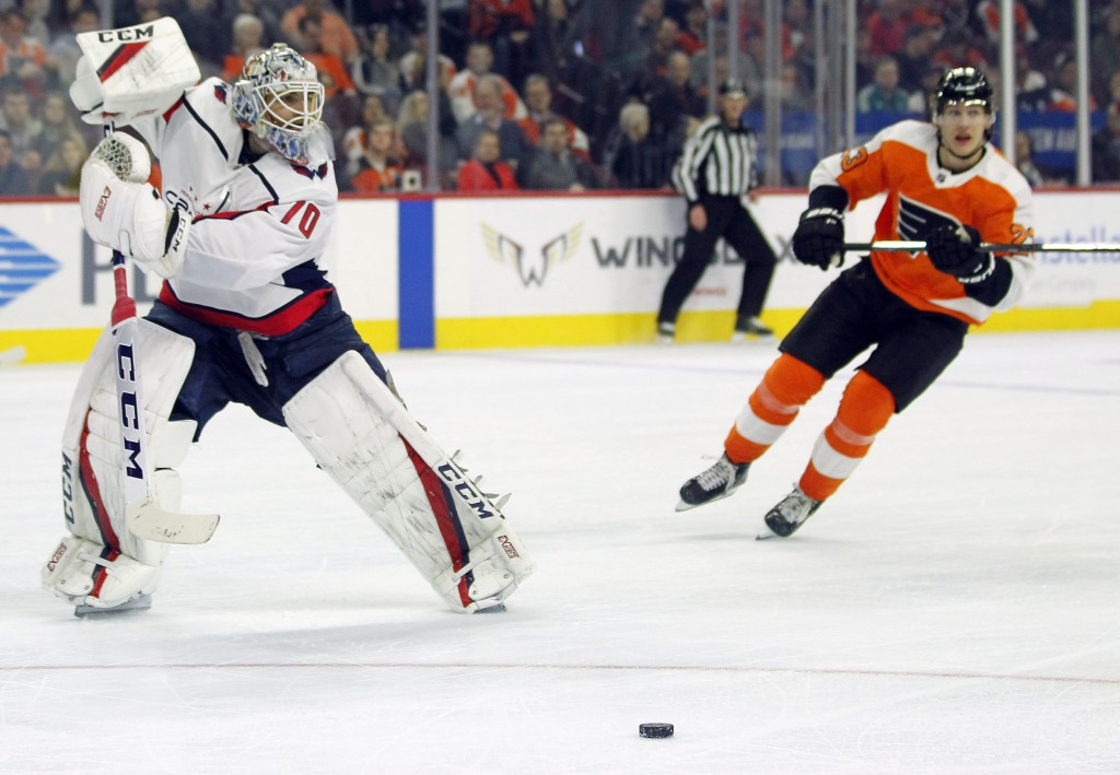 Washington Capitals goalie Braden Holtby is out of the crease as he directs the puck away from an approaching Philadelphia Flyers' Oskar Lindblom duri