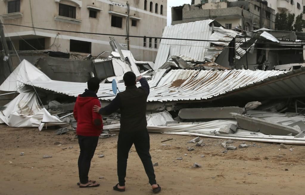 Palestinians inspect the damage of destroyed building belongs to Hamas ministry of prisoners hit by Israeli airstrikes in Gaza City early Friday Fri