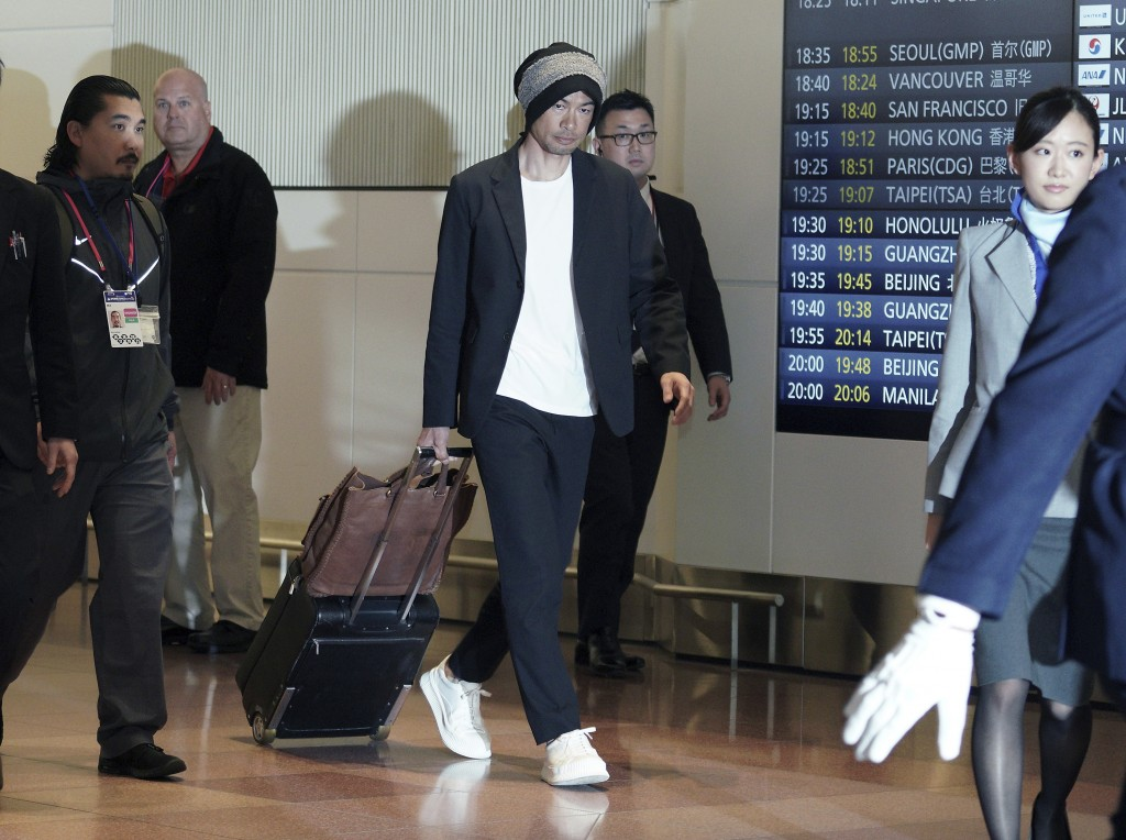 Seattle Mariners' Ichiro Suzuki, center, walks upon his team's arrival at Haneda international airport in Tokyo Friday, March 15, 2019. The Mariners w