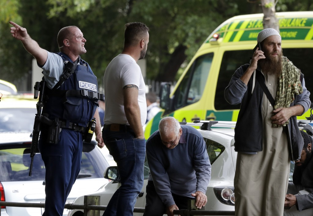 Police attempt to clear people from outside a mosque in central Christchurch, New Zealand, Friday, March 15, 2019. Many people were killed in a mass s