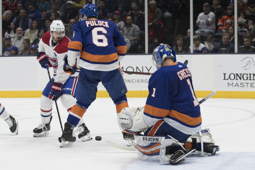 New York Islanders goaltender Thomas Greiss (1) and defenseman Ryan Pulock (6) make a save against Montreal Canadiens left wing Paul Byron (41) during